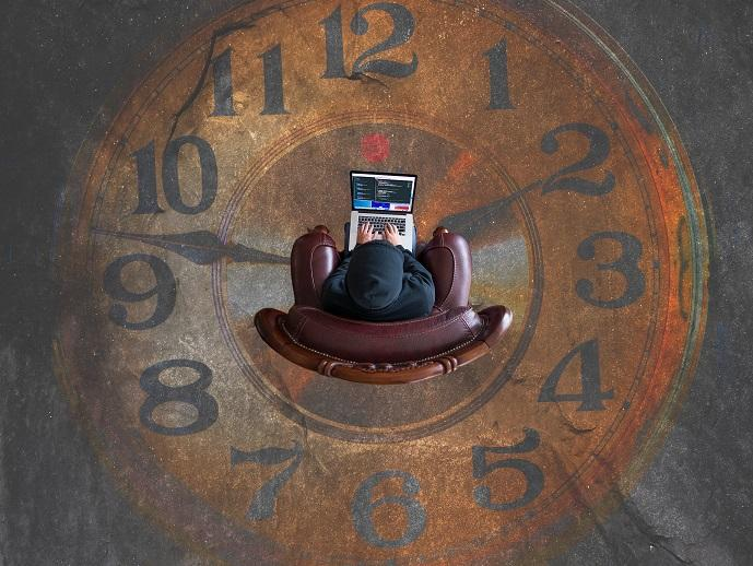 A person that's using a computer on the clock-styled floor.